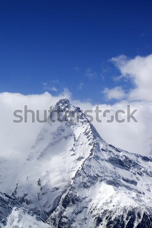 Snowy mountains in clouds Stock photo © BSANI