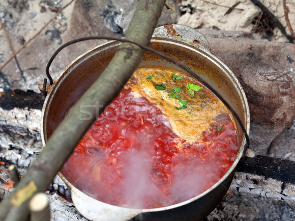 Borscht (Ukrainian traditional soup) cooking in sooty cauldron Stock photo © BSANI