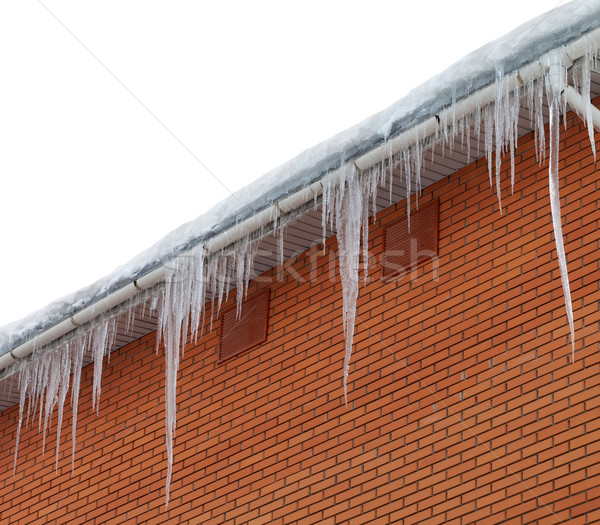 Stock photo: Snow-covered roof with icicles on white background