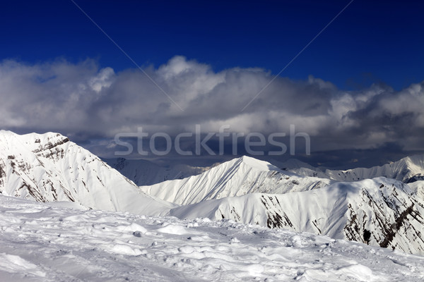Ski slope and beautiful snowy mountains in clouds. Stock photo © BSANI
