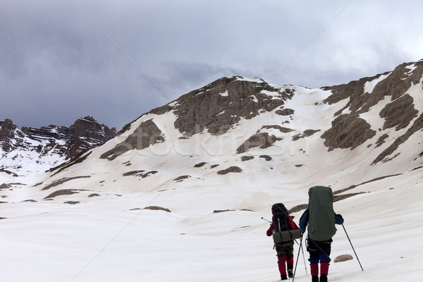 Two hikers on snowy plateau before storm Stock photo © BSANI