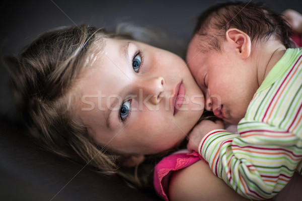 Little girl hugs her newborn sleeping sister Stock photo © bubutu