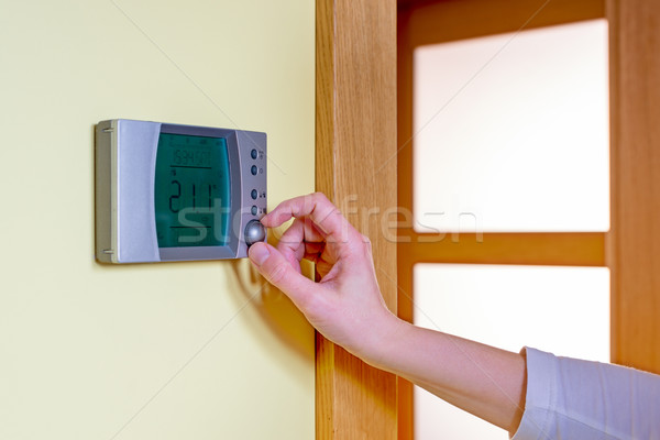 Closeup of a woman's hand setting the room temperature on a mode Stock photo © bubutu
