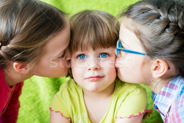 Embarrassed little girl kissed by two sisters. Stock photo © bubutu