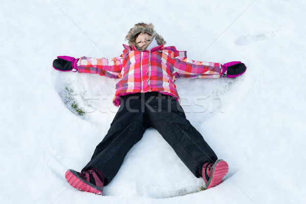 Little girl laying on snow and making angel Stock photo © bubutu