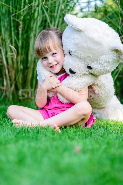 Little elfin girl sittinging in the grass with large teddy bear Stock photo © bubutu