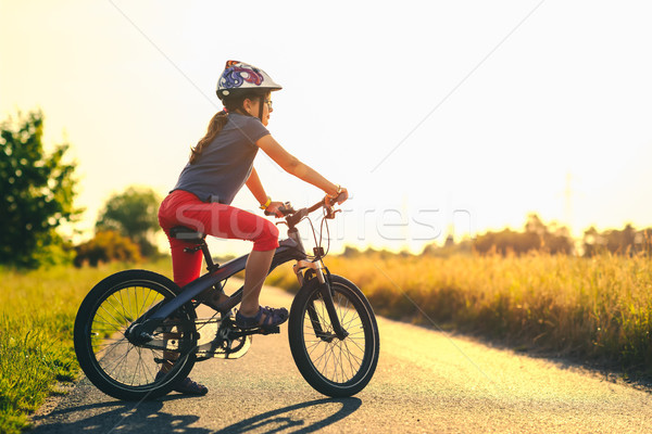 young girl on a mountain bicycle at sunset Stock photo © bubutu