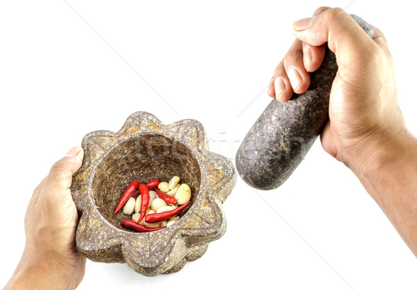 garlic and red chili pepper in stone mortar with hand holding Stock photo © Bunwit