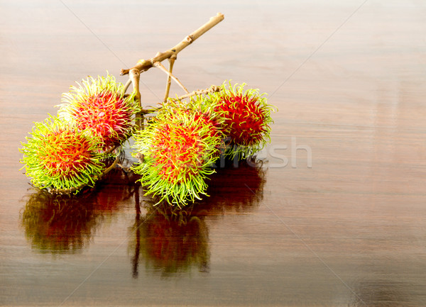 Rambutan on wooden table Stock photo © Bunwit