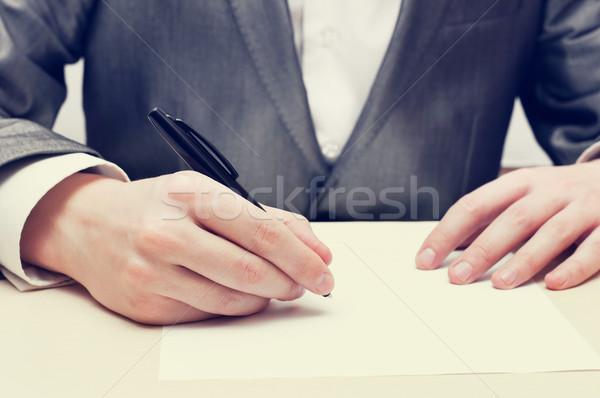 Businessman Writing On A Paper Stock photo © burtsevserge