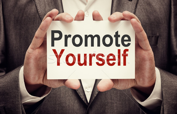 Businessman holding Promote yourself card Stock photo © burtsevserge