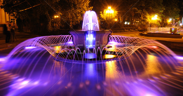 Colored water fountain at night Stock photo © byrdyak