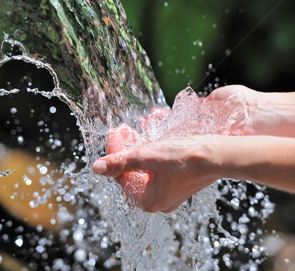 Stock photo: Woman's hands with water splash