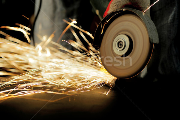 Worker cutting metal with grinder Stock photo © byrdyak