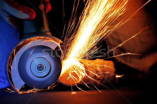 Worker cutting metal with grinder Stock photo © byrdyak