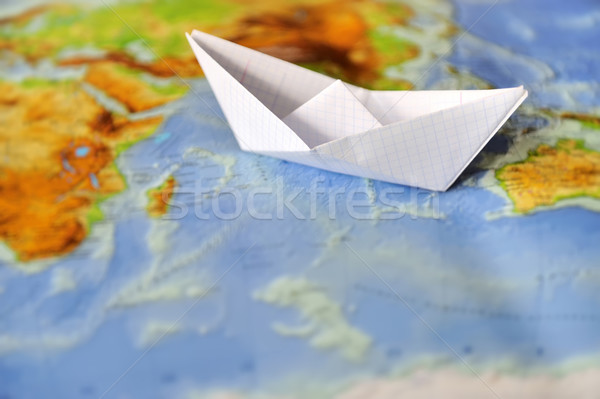 Paper boat on a background map of the world Stock photo © byrdyak