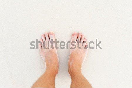 Male`s foot on sand Stock photo © byrdyak