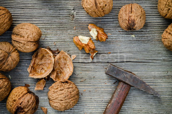 cracked walnuts and hammer on old wooden background Stock photo © c12