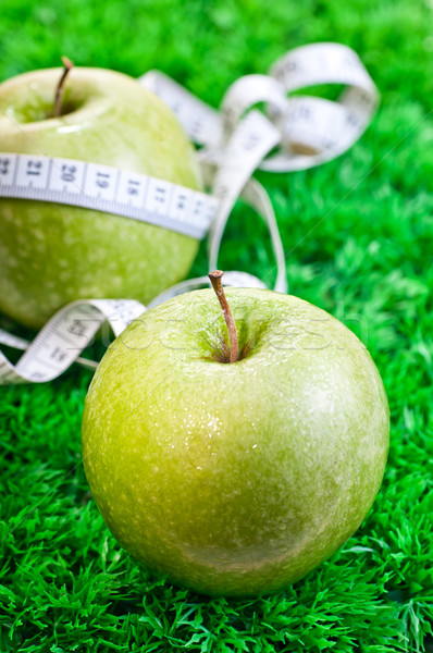 Two apples on the grass and one with a tape measure Stock photo © calvste