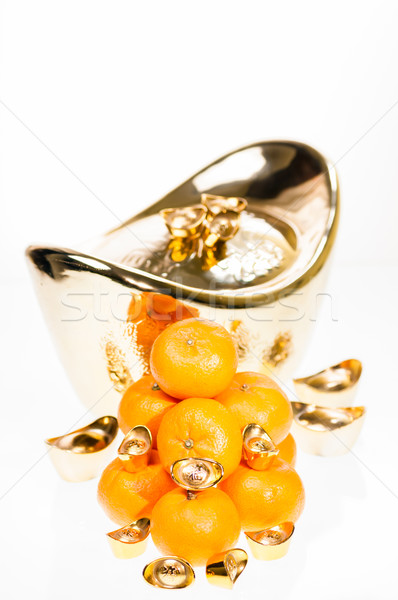 Golden ingots represent wealth and plump mandarin oranges signify good luck for Chinese New Year fes Stock photo © calvste