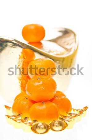 Good fortune with plump mandarin oranges and gold ingots close up Stock photo © calvste