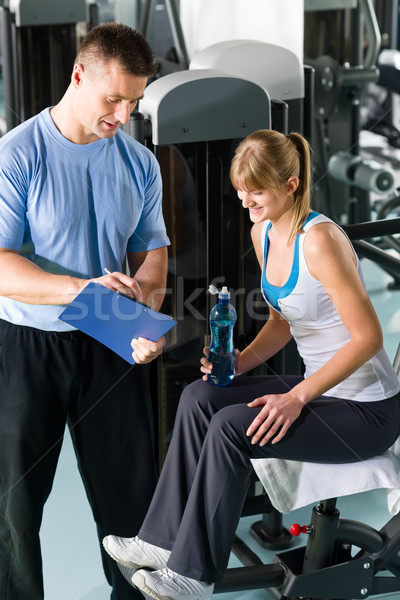 Stock photo: Personal trainer with young woman at gym