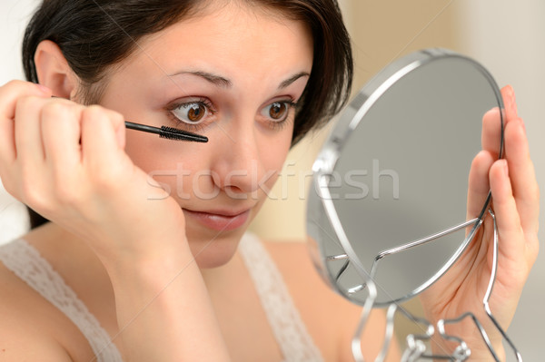 Attractive woman using mascara and handheld mirror Stock photo © CandyboxPhoto