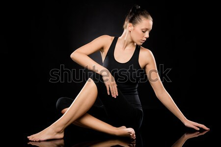 Attractive young woman in spine twisting pose Stock photo © CandyboxPhoto