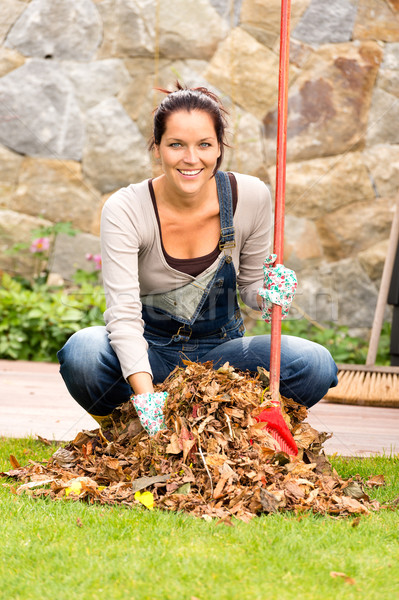 Cheerful woman sweeping leaves autumn pile backyard Stock photo © CandyboxPhoto