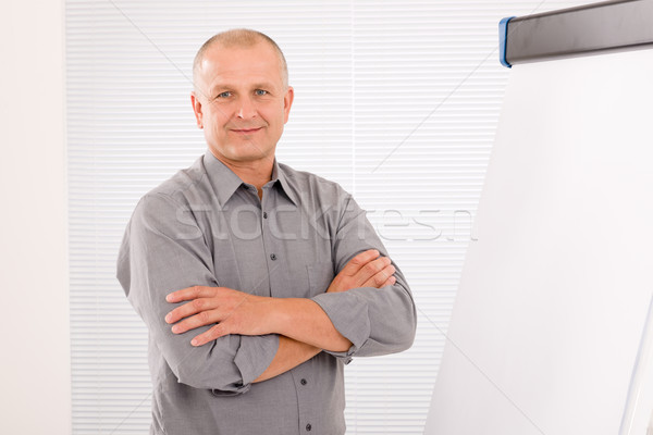 Mature businessman pointing at empty flip chart Stock photo © CandyboxPhoto