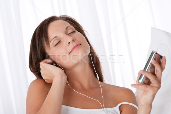 Young woman listening to music holding mp3 player Stock photo © CandyboxPhoto
