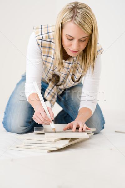 Home improvement - handywoman measuring tile Stock photo © CandyboxPhoto