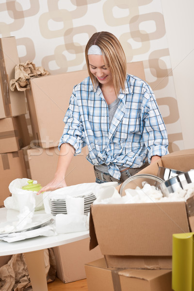 Moving house: Happy woman unpacking dishes Stock photo © CandyboxPhoto