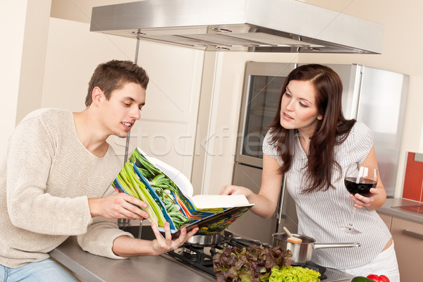 Young couple in kitchen choosing recipe from cookbook Stock photo © CandyboxPhoto