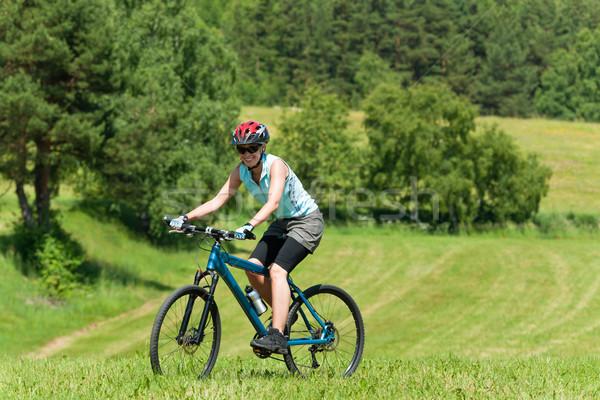 Sport mountain girl biking uphill sunny meadows Stock photo © CandyboxPhoto