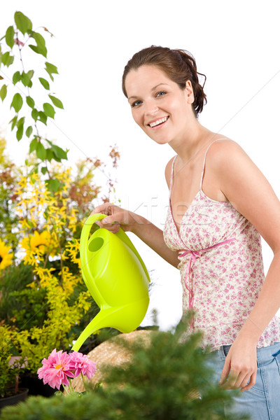 Stock photo: Gardening - woman with watering can and flowers