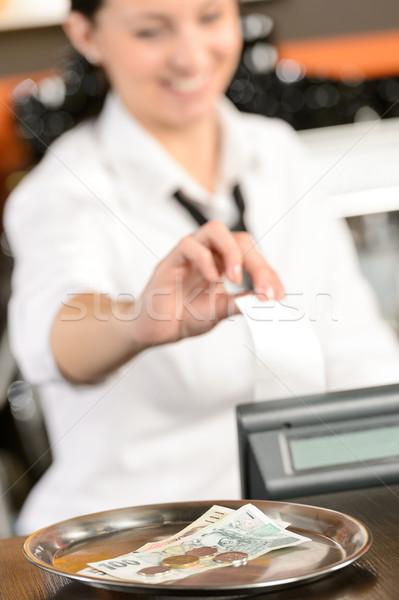 Stock photo: Young cashier giving receipt czech crowns