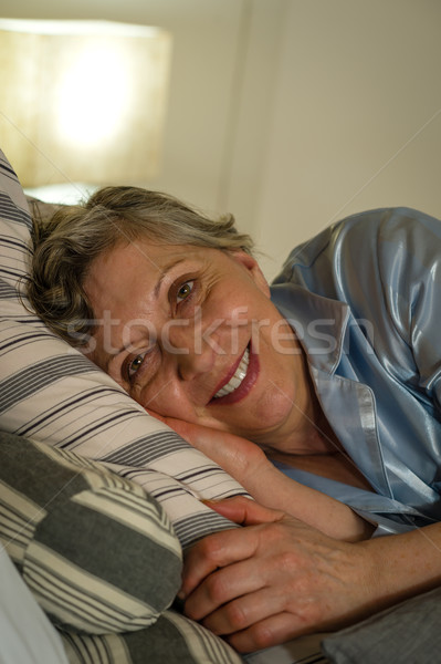 Retired smiling woman lying in bed Stock photo © CandyboxPhoto