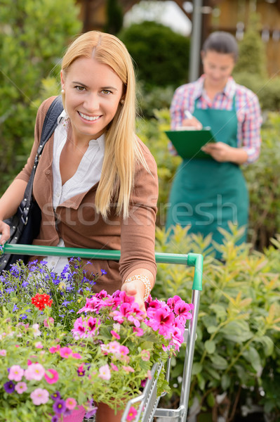 Woman put flowers in shopping cart greenhouse Stock photo © CandyboxPhoto
