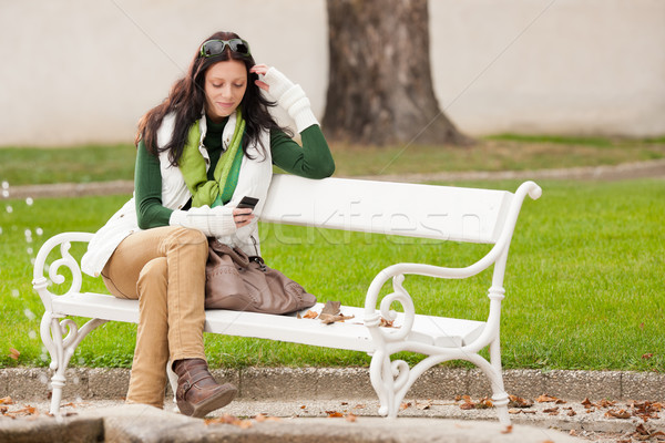 Autumn park bench young woman hold phone Stock photo © CandyboxPhoto