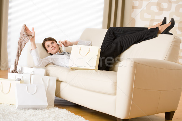 Young business woman lying down on sofa with shopping bag Stock photo © CandyboxPhoto