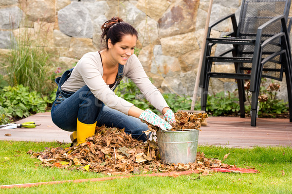 Smiling woman stuffing leaves pail gardening veranda Stock photo © CandyboxPhoto