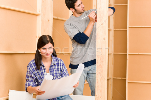 Stock photo: Home improvement young couple with blueprints