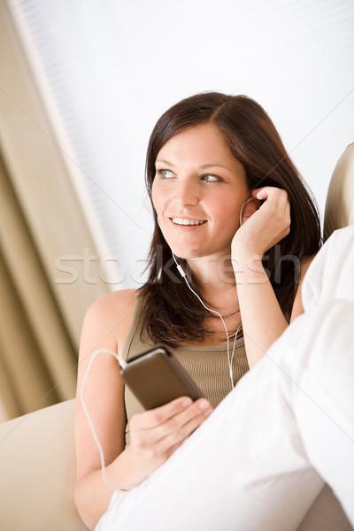 Nő tart zenelejátszó hallgat kanapé otthon Stock fotó © CandyboxPhoto