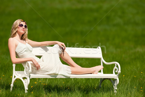 Spring - Young woman relaxing on bench in meadow Stock photo © CandyboxPhoto