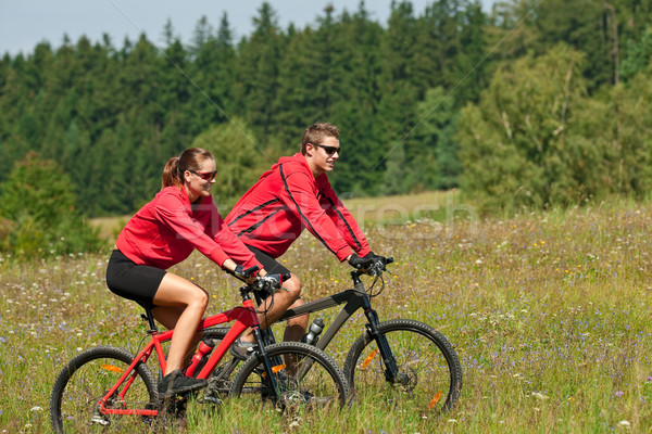 Young couple riding mountain bike in spring meadow Stock photo © CandyboxPhoto