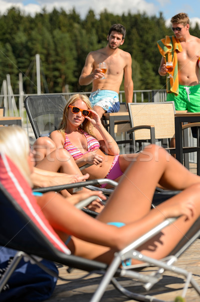 Women sunbathing on deckchair guys drinking beer Stock photo © CandyboxPhoto
