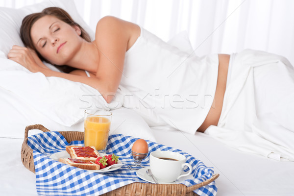 Woman sleeping in white bed, breakfast in foreground Stock photo © CandyboxPhoto