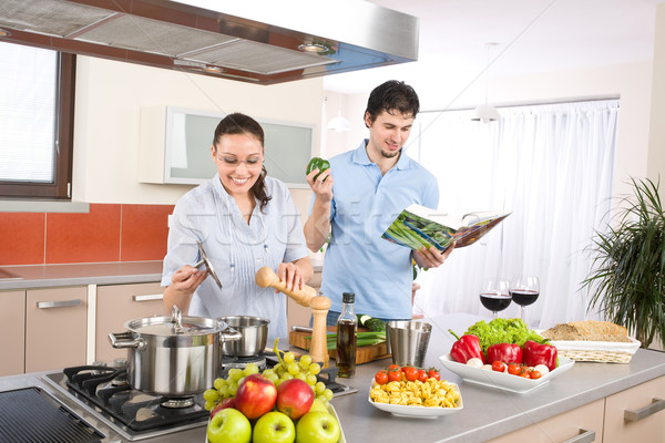 Young happy couple cook in kitchen with cookbook Stock photo © CandyboxPhoto