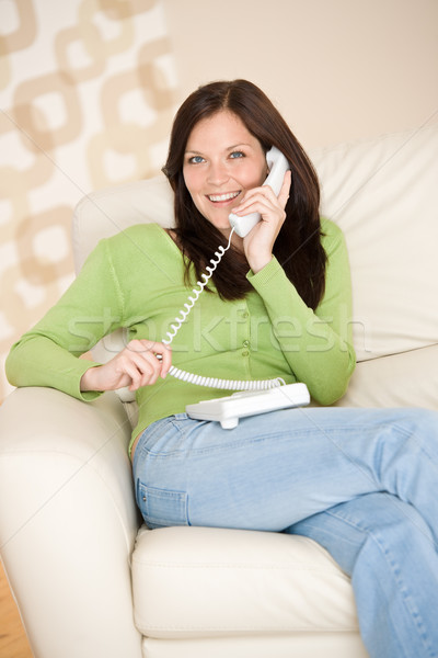 Stock photo: On the phone home: Smiling woman calling